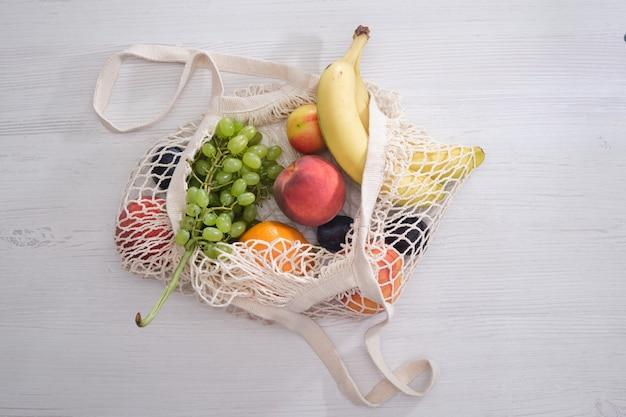 Obst und gemüse in einem netzbeutel auf einem hölzernen hintergrund
