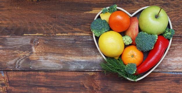 Obst und gemüse in herzförmiger holzkiste. brokkoli, äpfel, pfeffer, mandarine über holztisch. biokost-konzept mit copyspace.