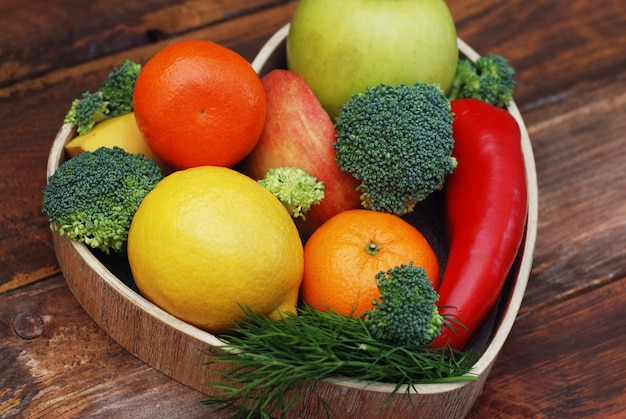 Obst und gemüse in herzförmiger holzkiste. brokkoli, äpfel, pfeffer, mandarinen.
