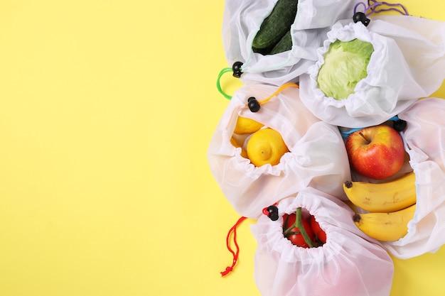 Obst und gemüse in wiederverwendbaren, umweltfreundlichen netzbeuteln auf leuchtend gelbem hintergrund. platz für text, zero-waste-konzept, verschmutzung stoppen. ansicht von oben