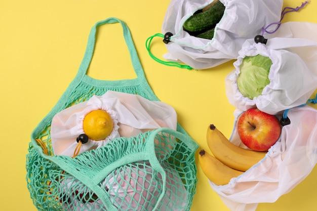 Obst und gemüse in wiederverwendbaren, umweltfreundlichen netzbeuteln auf leuchtend gelbem hintergrund. zero-waste-konzept. ansicht von oben