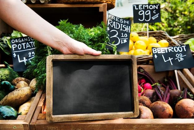 Obst-und gemüsehändler, der organisches neues landwirtschaftliches produkt am landwirtmarkt verkauft