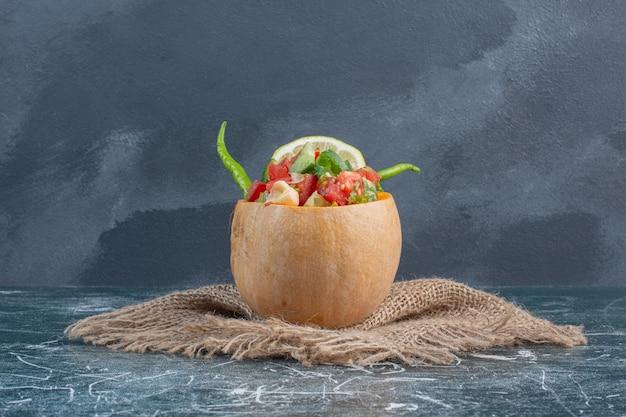 Obst- und gemüsesalat in einem kleinen geschnitzten kürbis.