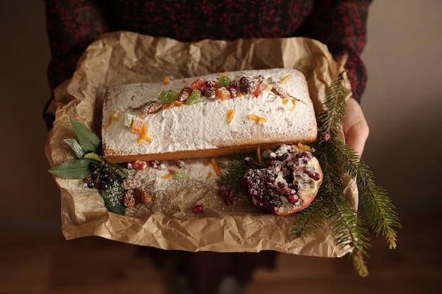 Obstkuchen bestäubt in scheiben geschnitten mit zuckerguss, nüssen, granatapfelkernen und trockener orangennahaufnahme. weihnachts- und winterferien hausgemachter kuchen