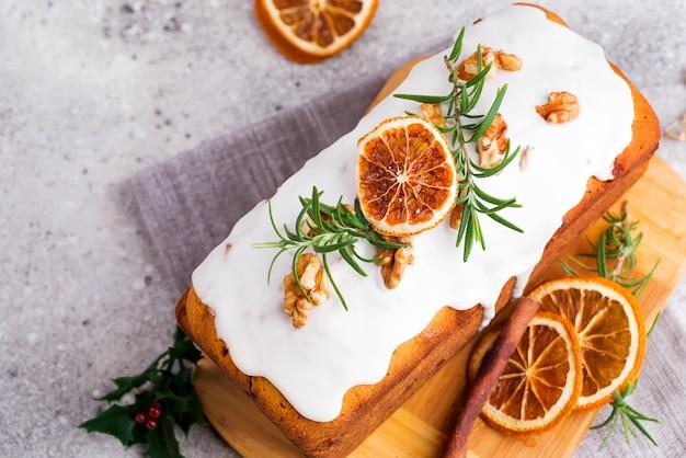 Obstkuchen mit zuckerguss, nüssen und trockenem orangenstein bestäubt, flach legen. weihnachts- und winterferien hausgemachten kuchen