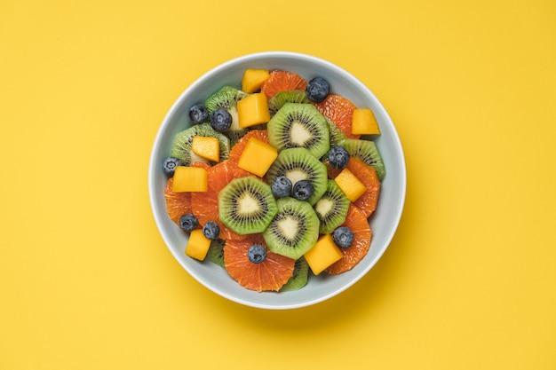Obstsalat aus roten orangen, kiwi, mango und beeren isoliert auf gelbem hintergrund