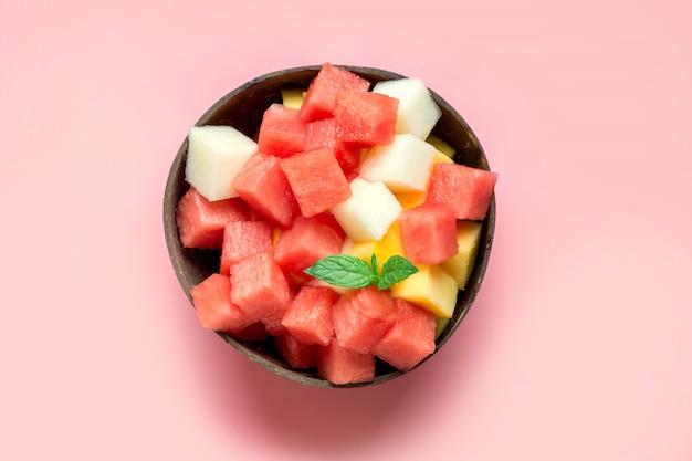 Obstsalat der wassermelone, der melone und der mango in der kokosnussschüssel auf rosa hintergrund.