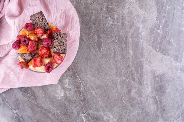 Obstsalat im glasbecher mit schokoladenkeksen