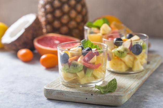 Obstsalat in den gläsern, frische sommernahrungsmittel, gesunde organische orange kiwiblaubeerananaskokosnuss. ansicht von oben