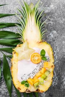 Obstsalat in der hälfte der ananas flach legen