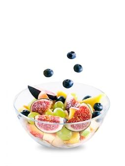 Obstsalat in einer glasschüssel lokalisiert auf weißem hintergrund. blaubeeren fallen in die schüssel.