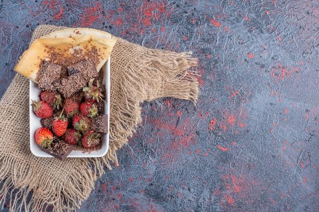 Obstsalat in einer tasse mit bitterschokolade.