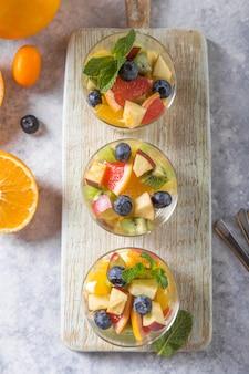 Obstsalat in gläsern, frische sommernahrungsmittel, gesunde organische orange kiwiblaubeerananaskokosnuss