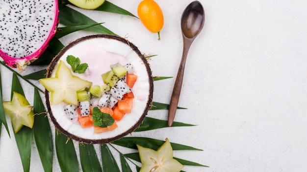Obstsalat in kokosnussplatte mit löffel