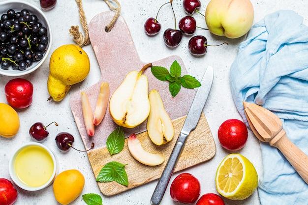 Obstsalat kochen. schneiden von früchten auf einem brett, draufsicht. gesundes veganes lebensmittelkonzept.