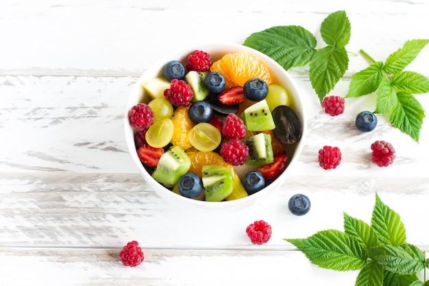 Obstsalat mit banane, kiwi, trauben, himbeeren, blaubeeren in einer schüssel auf einem weißen holztisch.