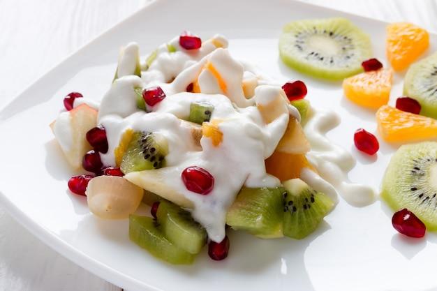 Obstsalat mit der weißen platte der eiscreme verziert mit beerengranatapfel