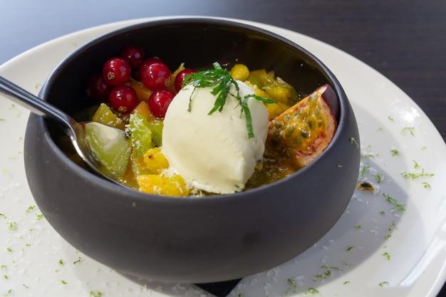 Obstsalat mit eis in einer schwarzen schüssel auf einem weißen teller in einem restaurant