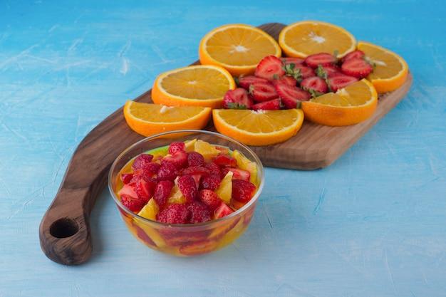 Obstsalat mit erdbeeren und orangen mit obstbrett beiseite