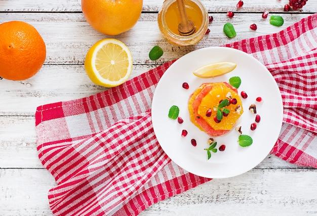 Obstsalat mit grapefruit und orange, granatapfelkernen, honig und zitrone, dekoriert mit minze. draufsicht
