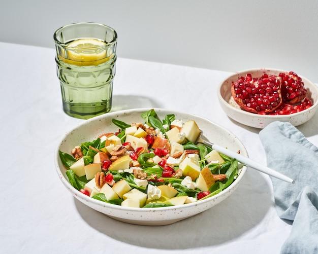 Obstsalat mit nüssen, ausgewogenes essen, sauberes essen. spinat mit äpfeln, pekannüssen und feta, garniert mit granatapfelkernen in schüssel auf tisch mit weißer tischdecke. hartes licht, schatten, seitenansicht