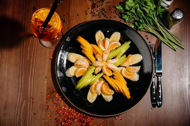 Obstsalatmischung, fruchtdessert - geschnittene banane, mandarine, orange, apfel. draufsicht
