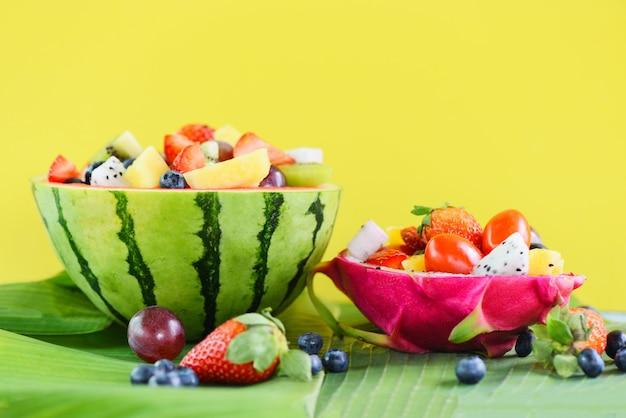 Obstsalatschüssel diente in den frischen sommerfrüchten der orange kiwiblaubeeren-traubenananastomaten-zitrone des drachefrucht- und wassermelonengemüses des gesunden lebensmittels erdbeertropischen auf bananenblatt