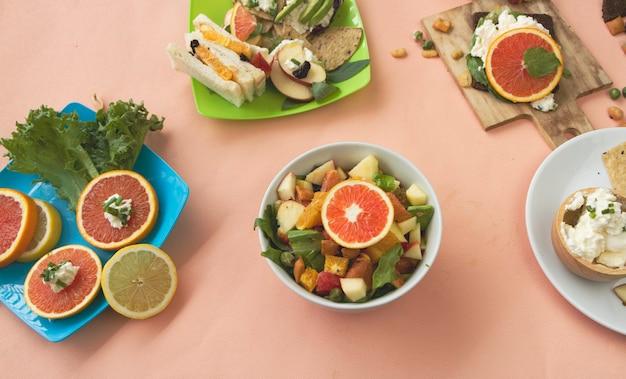 Obstsalatschüssel in der mitte von canape mit sandwichteller, frischkäseschale und geschnittenem orangenteller, auf pastellfarbenem hintergrund