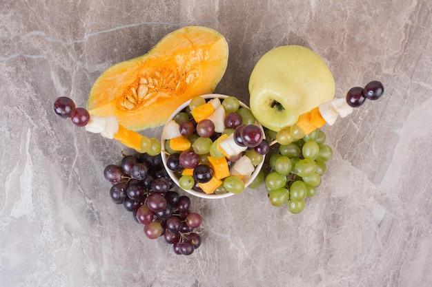 Obstschale und frisches obst auf marmoroberfläche.