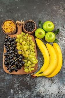 Obstschalen mit getrockneten früchten äpfel bananen und trauben auf dem küchenbrett