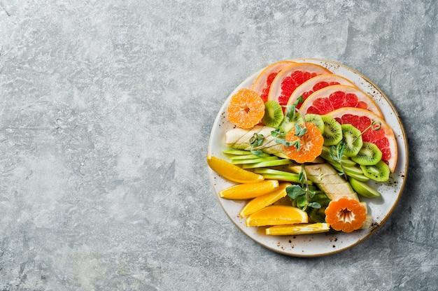 Obstteller, grapefruit, mandarine, kiwi, orange, banane, apfel.