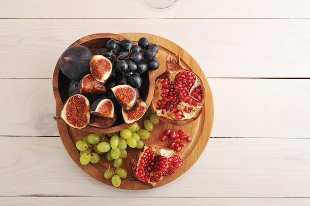Obstteller mit feigen, trauben, granatapfel auf holzoberfläche