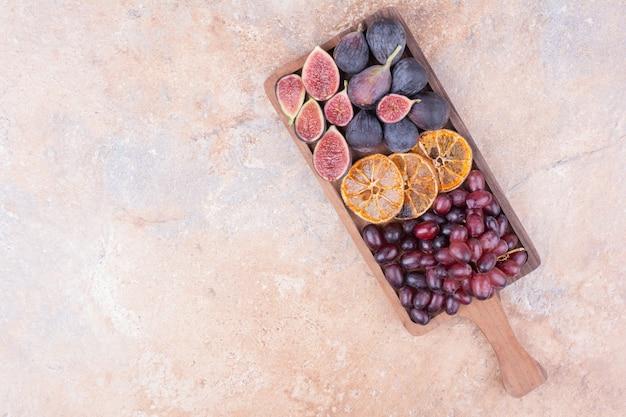 Obstteller mit lila feigen, orangen- und kornelkirschenbeeren.