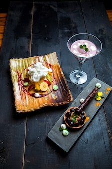 Obstteller mit sahne, schokoladen-tartaleta und heidelbeer-pouding