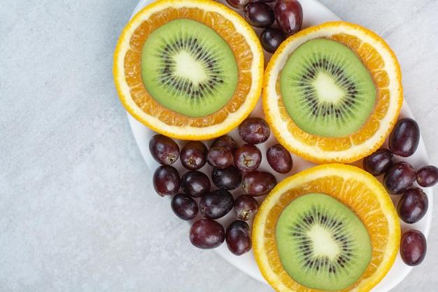 Obstteller mit trauben, kiwi und orangenscheiben. foto in hoher qualität
