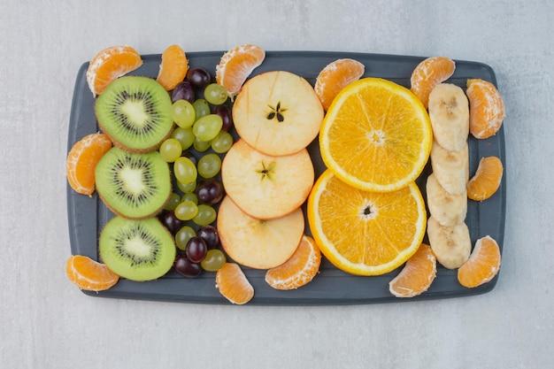 Obstteller mit zitrusfrüchten, trauben, bananen- und kiwischeiben. foto in hoher qualität