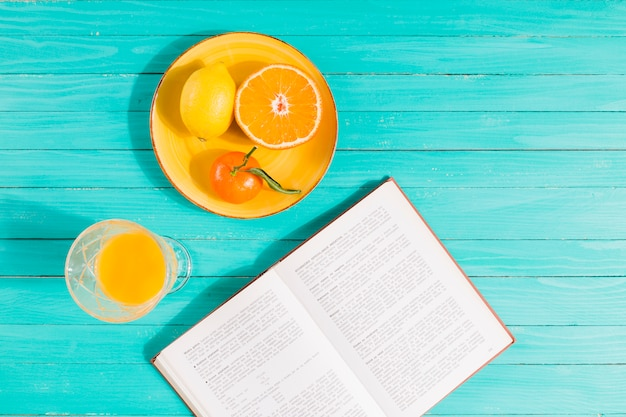 Obstteller, saftglas und buch auf dem tisch