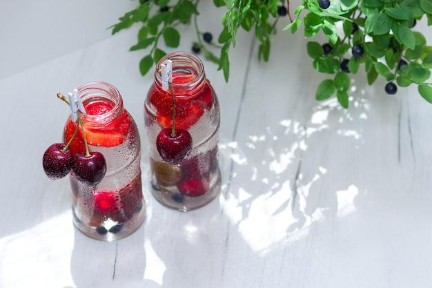 Obstvielfalt mit detox-wasser in kleinen glasflaschen. erfrischende sommergetränke. gesundes ernährungskonzept.