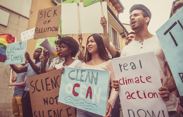 Öffentliche demonstration auf der straße gegen globale erwärmung und umweltverschmutzung. gruppe multiethnischer menschen, die gegen den klimawandel und plastische probleme in den ozeanen protestieren