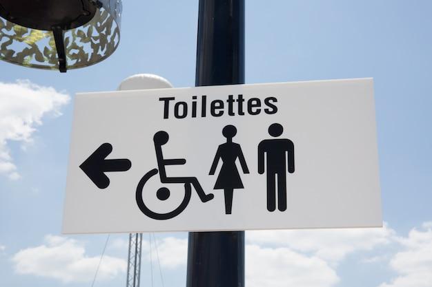 Öffentliche schwarzweiss-toiletten unter hellem blauem himmel