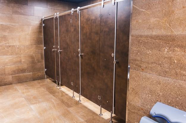 Öffentliche toilette toilette mit braunen türen in einer reihe.