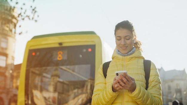 Öffentliche verkehrsmittel der stadt. junge stilvolle frau, die auf der tramstation hält smartphones und wartet auf tram steht Premium Fotos