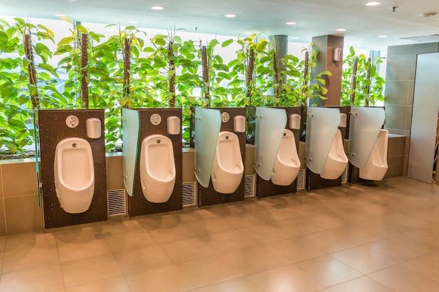 Öffentlicher herrentoilettenraum mit elektronischem sensor der technologie und grünpflanze für entspannen sich