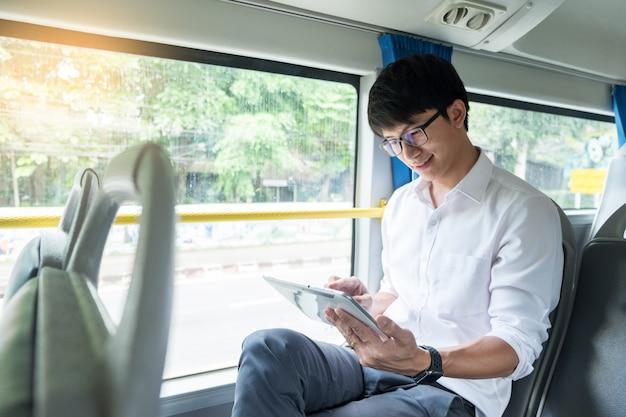 Öffentlicher verkehr, mobilität. hübsches junges geschäftsmannlesebuch auf bus