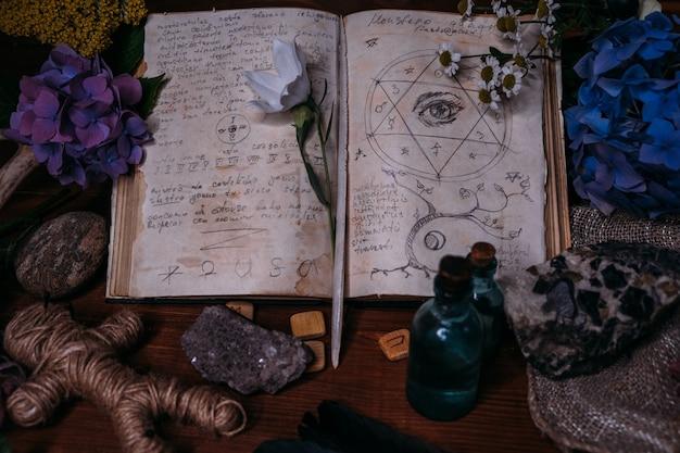 Öffne ein altes buch mit zaubersprüchen, runen, schwarzen kerzen und kräutern auf dem hexentisch.