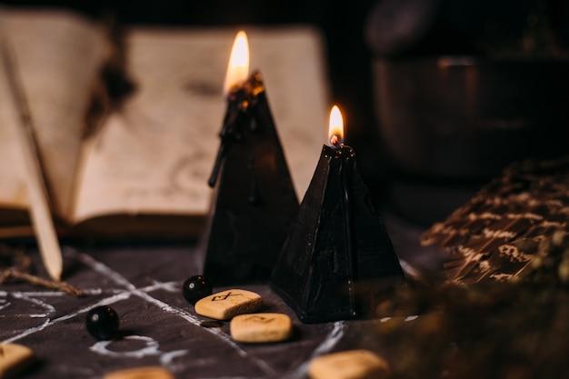 Öffne ein altes buch mit zaubersprüchen, runen und schwarzen kerzen auf dem hexentisch. okkultes, esoterisches, wahrsagungs- und wicca-konzept. halloween-szene