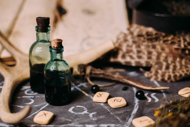 Öffne ein altes buch mit zaubersprüchen, runen und schwarzen kerzen auf dem hexentisch. okkultes, esoterisches, wahrsagungs- und wicca-konzept.