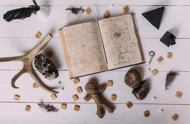 Öffne ein altes buch mit zaubersprüchen, runen und schwarzer kerze
