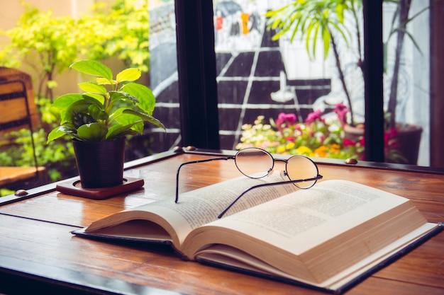 Öffnen sie altes buch mit gläsern auf hölzerner tabelle im café