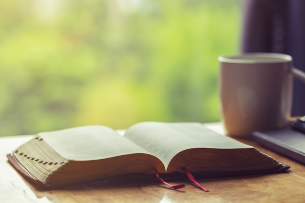 Öffnen sie bibel mit einem tasse kaffee für morgenandacht auf holztisch mit fensterlicht